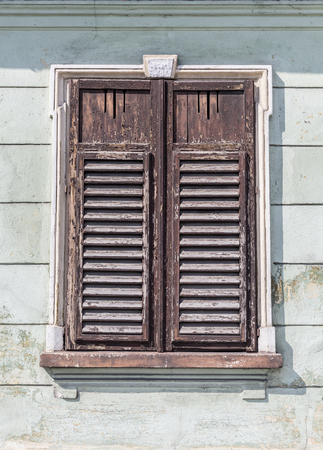 window frame: The old window with closed shutters on an old house. Vintage background, texture.