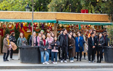 Barcelona, Spain December 17, 2018: tourists on group tours from the East on Barcelona street. Spain