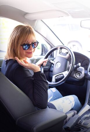 woman in car indoor keeps wheel turning around smiling looking at passengers in back seat Archivio Fotografico