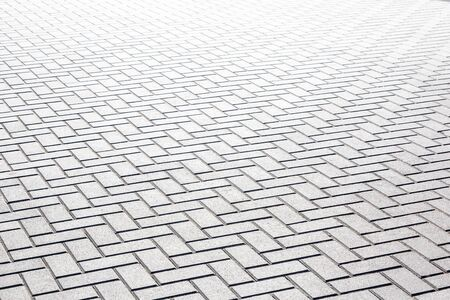 Texture of gray patterned paving tiles on the ground of street, perspective view.