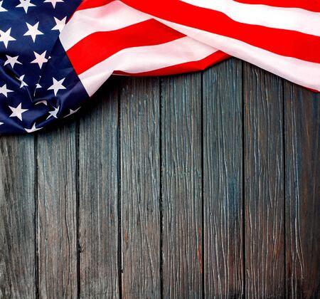 Bandera de Estados Unidos arrugada. Bandera de Estados Unidos sobre fondo de madera. Bandera nacional en suelo blanco. Unidad y orgullo.