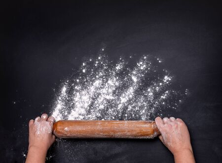 hands keep rolling pin with flour on dark black table