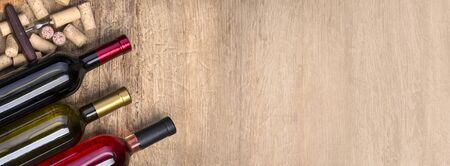 wine bottle, glass and  corks on wooden table background with copy space