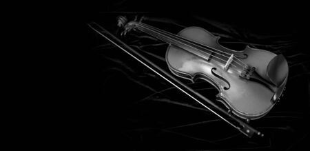 Shiny violin and bow isolated on black velvet background with copy space