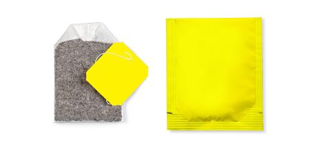 Teabag with yellow , label. Top view. Isolated on a white.  Imagens