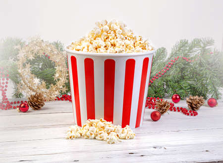 Popcorn in stripped bowl over wooden background Christmas Background