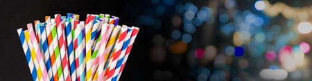 Paper straw of different colors on a dark background with a copy space