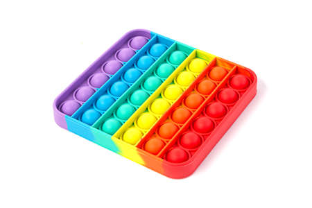 Pop It Simple Dimple - silicone sensory anti-stress Fidget toy colorful rainbow game isolated on white background, copy space.