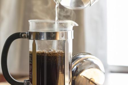 醸造での暖かい朝の光の中、フランス語を押すコーヒー