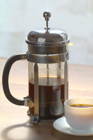 caffeinated: Coffee brewing in a French press in warm morning light;