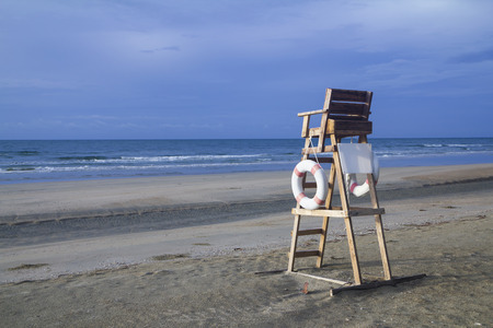 lifeguard chair on an emply stormy beach and overcast cloudy sky on a bad weather day