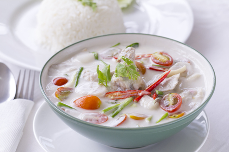 Thai Food, Tom Kha Gai, chicken soup in coconut cream in white with steamed rice beside. Stock Photo