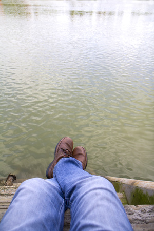 quite time: Man with brown shoes taking a rest and relax on the river bank in selfie style