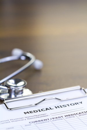 resonator: Stethoscope and Medical History Report Isolated on Brown Wooden Desktop with Upper Space