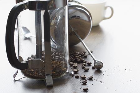 Grano de café molido grueso en la taza clara de la prensa francesa en la sobremesa de madera Foto de archivo