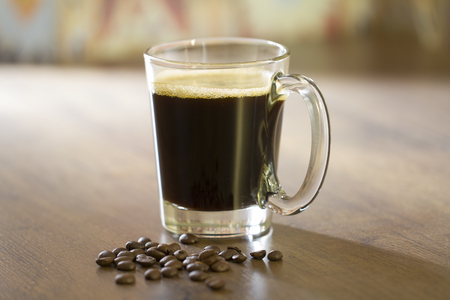 Hot black americano coffee in transparent glass cup presented in center of the frame