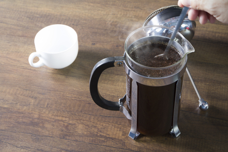 Coffee brewing preparation with french press coffee plunger mug as brewing instrument with a spoon stirring in motion blur and steam over the hot drink surface. Presented in warm tone.