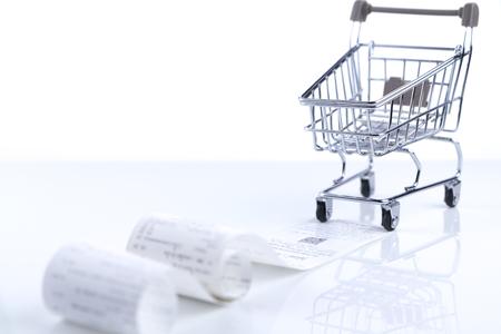 Carrito de compras va a moverse a lo largo de la factura o la cinta de recibo de pago aislada en el piso blanco brillante y fondo blanco.