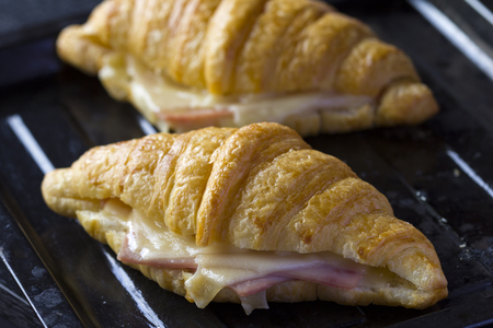 Newly baked butter croissant with ham and cheese sandwiches on old black baking tray.