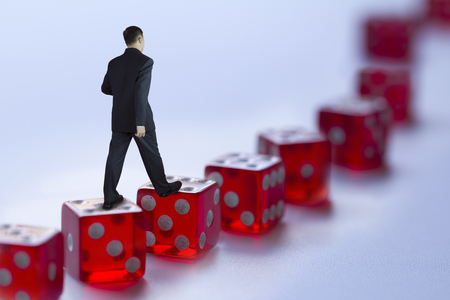 Businessman walking along red dices path isolated on white showing business management or risky business concept