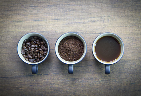 Three cups of difference stages of coffee preparation or the making of coffee drink isolated on brown wooden surface