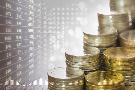 Stacks of coins money and faded stock trading board in golden light and soft bokeh with digital world map on background