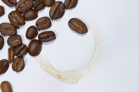 Coffee beans and coffee stain isolated on white paper background with copy space