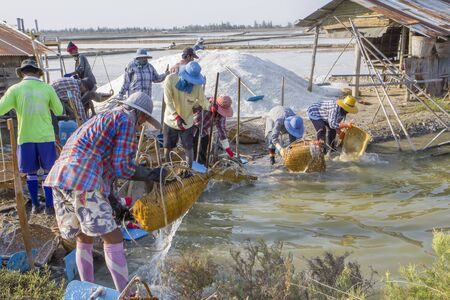 Thailand, Phetchaburi - January 18, 2013: Sea salt farmers washing salt buckets and tools in the pond after finishing their job in the field