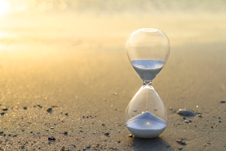 Hourglass close up in a warm golden morning sunlight on a sandy beach starting time for a new day or running of time with side copy space. Stock Photo
