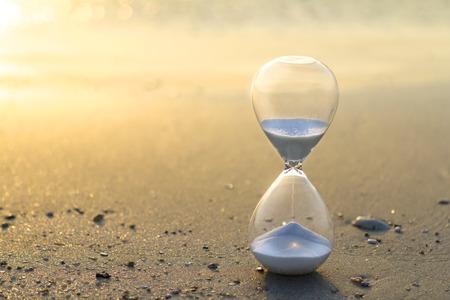 Klepsydra z bliska w ciepłym, złotym porannym słońcu na piaszczystej plaży, czas rozpoczęcia nowego dnia lub upływ czasu z kopią boczną.