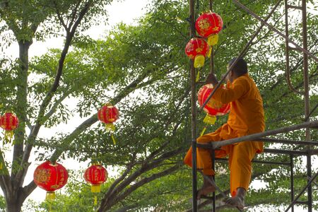 Nonthaburi, Thailand - 4 February 2018: Young Thai-Chinese buddhist monk on a scaffolding hanging red lanterns on the trees as a decoration accessory in preparation for the up-coming Chinese new year