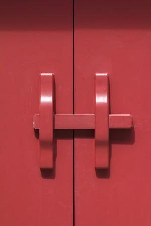 Red wooden door in status of being locked 写真素材