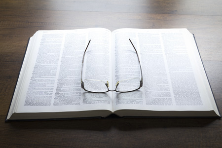 Black eyeglasses lying on an opened thick book isolated on black background in warm tone.