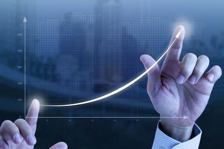 Close up of a businessman's hands drawing an exponential line curve showing of business growth and success rapidly. Foto de archivo