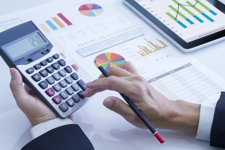 Uomo d'affari utilizzando la calcolatrice rivedendo una relazione finanziaria per un ritorno sull'investimento o analisi del rischio di investimento.