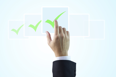 Closeup on a hand of businessman touching digital checkboxes as checklist items isolated on light blue gradient background