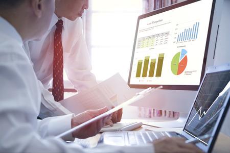 Dos hombres de negocios asiáticos analizando la comparación de préstamos comerciales en computadoras de escritorio y portátiles con coloridos gráficos de barras y tartas. Foto de archivo