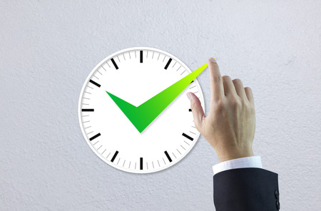 Hand of businessman makes a check mark on a clock face in concept of time that is under control.