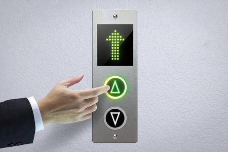 Mano de un hombre presionando el botón del elevador para los siguientes niveles en concepto de más avance hacia el éxito.
