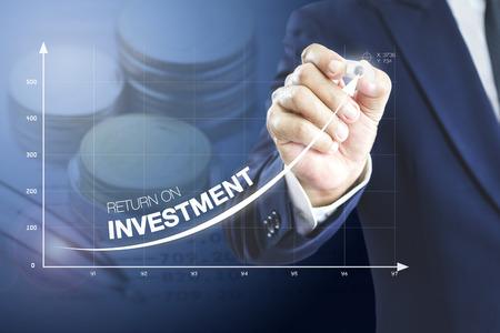 Uomo d'affari che disegna una curva esponenziale di un progresso nelle prestazioni aziendali, ritorno sull'investimento - ROI, su una presentazione su schermo virtuale. Archivio Fotografico