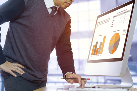 Businessman looking into a modern computer screen and financial report reviewing a business performance with colorful graphs. Stock Photo