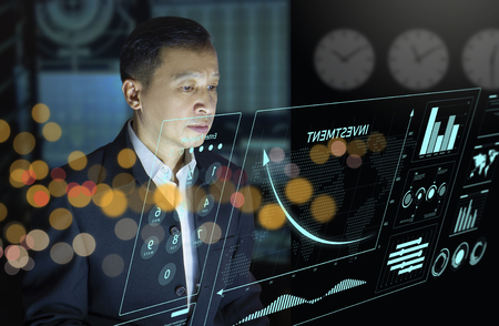 Businessman in front of modern virtual touch screen analysing on investment risk management and return on investment analysis or business performance. Reklamní fotografie