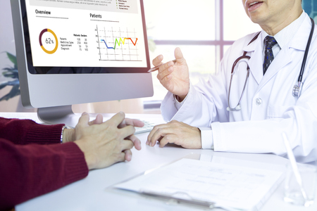 Male doctor giving a consultation to his patient with medical diagnosis information on computer screen in the office.