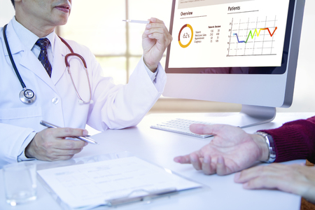 Male doctor checking a thermometer and giving a consultation to his patient with medical diagnosis information on computer screen in the office.