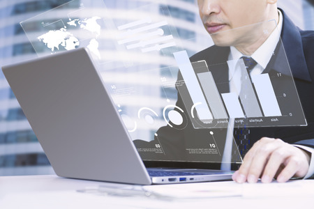 Businessman or analyst looking into a laptop computer notebook deeply reviewing a financial reports for a return on investment or investment risk analysis.
