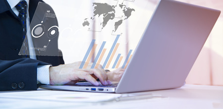 Businessman or analyst with concentration typing on laptop computer notebook for financial reports analysis and return on investment, ROI, or investment risk. Side copy space included.