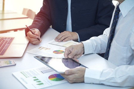 Businessman is deeply reviewing a financial reports for a return on investment or investment risk analysis on a laptop computer notebook.