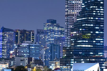 High-rise buildings with electric light in an urban cityscape in blue twilight background