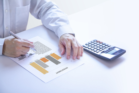 Businessman or analyst partially cropped at his hands holding a pen on an investment report, analysing on investment risk and a return on investment - ROI. Side copy space included. Reklamní fotografie
