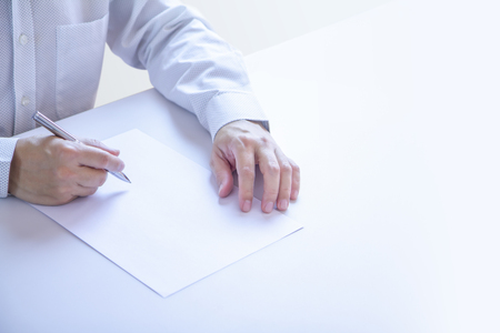 Business man partially cropped at his hands holding a pen with writing gesture on a plain blank white paper document as a blank mock-up template to be refilled with any information.